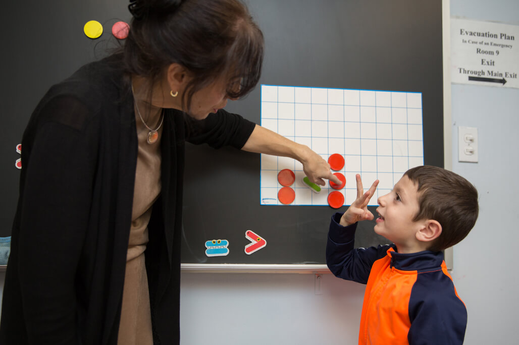 Teacher and elementary student working out a math enrichment exercise at the chalkboard of a classroom