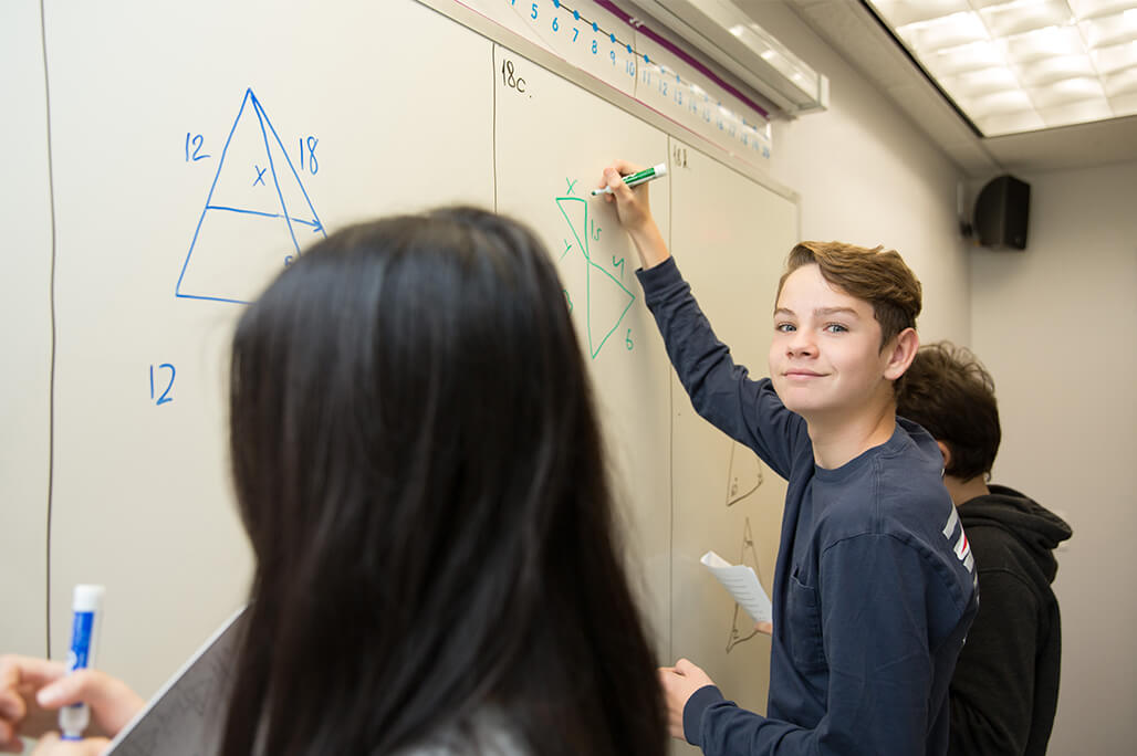 Students working out math problem at the whiteboard of a classroom
