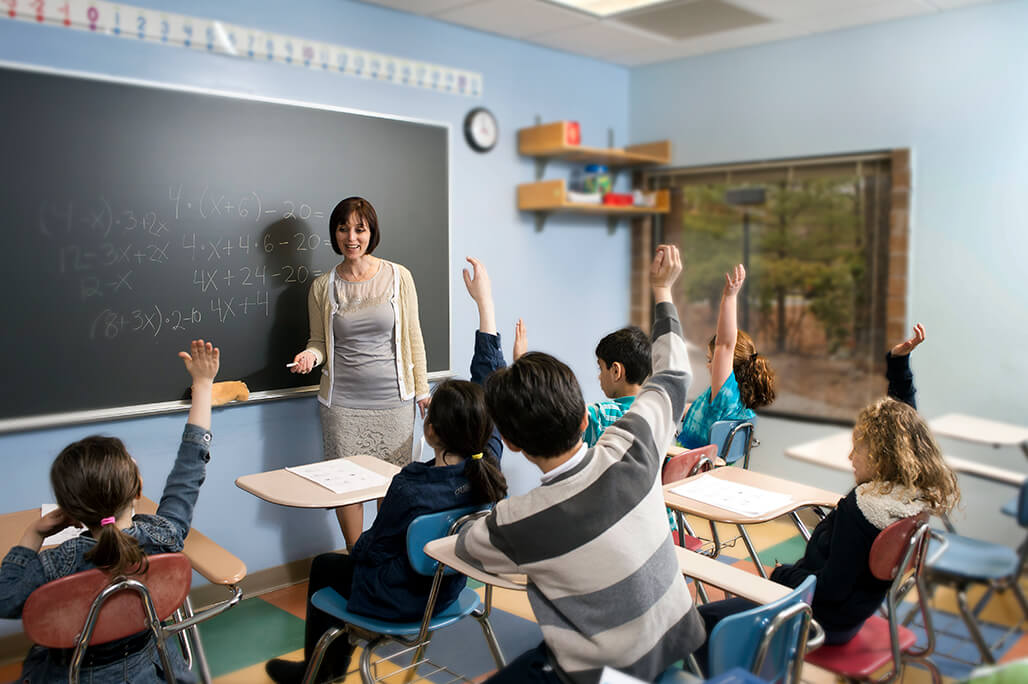 Female teacher working with a group of elementary grade students who are all raising their hand to answer a question.