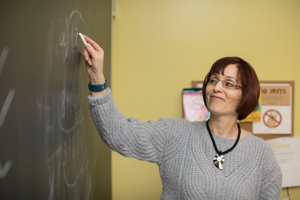 RSM teacher writing on a chalkboard